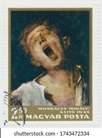 ST. PETERSBURG, RUSSIA - MAY 28, 2020: A postmark printed in HUNGARY, shows painting Yawning Boy by Mihaly Munkacsi (1844-1900), circa 1966