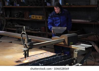 St. Petersburg, Russia - May 30, 2017: Operator makes cutting metal plate using a CNC plasma cutter machine.