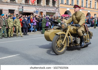 St. Petersburg, Russia May 9, 2017: A man in the uniform of a Soviet Red Army soldier from the times of the Second World War on an old motorcycle rides along Nevsky Prospekt