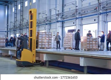 St. Petersburg, Russia - November 21, 2008: Loading and unloading operations inside the warehouse, a forklift puts pallets on an elevated platform where loaders men use a hand pallet truck.