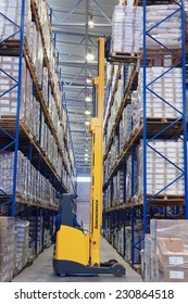 St. Petersburg, Russia - November 21, 2008: Yellow pedestrian stacker lifts pallet with boxes on shelves. Forklift pallet truck lifts pallet in narrow aisle warehouse. Fork lift truck with raised fork
