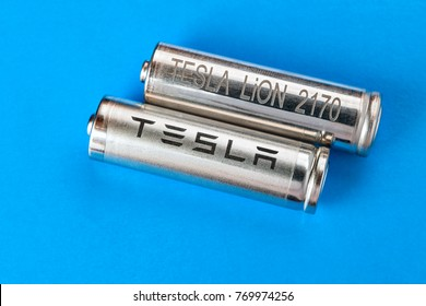 St. Petersburg, Russia - November 30, 2017: Two cylindrical battery with Tesla logo, for a pack of cells, on light blue background.