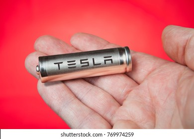 St. Petersburg, Russia - November 30, 2017: Cylindrical lithium-ion battery cell for electric car Tesla in hand, red background.