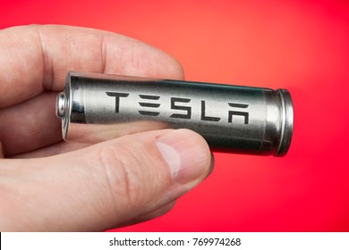 St. Petersburg, Russia - November 30, 2017: Lithium-ion battery for powering Tesla cars in human hand, on red background.