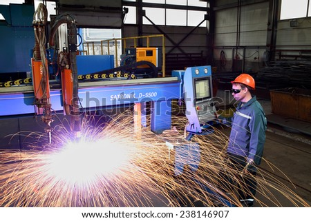 St. Petersburg, Russia - October 10, 2014: Factory production of metal, worker working in a helmet and goggles, controls the plasma metal cutting, standing next to the display remote control.