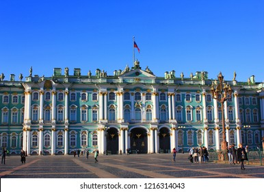 ST. PETERSBURG, RUSSIA - OCTOBER 15, 2018: Winter Palace and Hermitage Museum Building at Palace Square. Facade Architecture of Old Historical City Landmark with Russian Flag and Tourists on Sunny Day