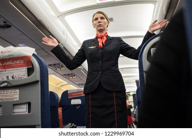 """St. Petersburg, Russia- October 8, 2018: a flight attendant of the airline """"Ural Airlines"""" instructs the passengers of the liner on safety and tells how to use the device during an emergency."""