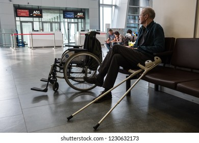 St. Petersburg, Russia - October 8, 2018: An elderly bald disabled person in the departure lounge before boarding a plane looks at the scoreboard with a flight schedule.