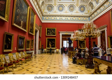 ST. PETERSBURG, RUSSIA - OCTOBER 8, 2017: Tourists enjoying the gigantic paintings on the wall of the historical Winter Palace wholeheartedly.