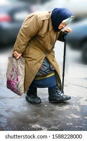 St. Petersburg, Russia, September 13, 2008. An old hunched woman in poor rags with a stick and a bag is walking along the sidewalk