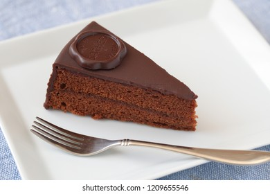 ST. PETERSBURG, RUSSIA - SEPTEMBER 25, 2018: Slice of Sacher torte on a plate closeup. This chocolate cake was invented by Franz Sacher in 1832, and now December 5th is National Sachertorte Day in US