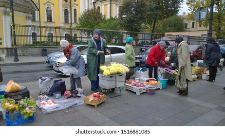 St. Petersburg, RUSSIA - September 28, 2019: Old women pensioners sell flowers, fruits and vegetables near the subway.  Local city market, fair.  Concept of poverty and a small pension. Street trading