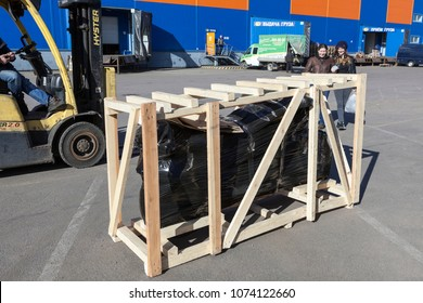 ST. PETERSBURG, RUSSIA-CIRCA APR, 2018: Motorbike unit delivery for client in crate by freight company. Wooden box with wrapped vehicle is ready for loading in truck