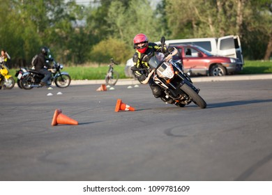 ST. PETERSBURG, RUSSIA-CIRCA MAY, 2018: Motorbiker drives through cones with drift on urban square. Free skill training as gymkhana for all riders