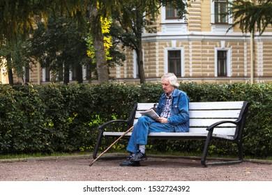 ST. PETERSBURG, RUSSIA-SEPTEMBER 10, 2019: an Elderly man solves crosswords on a bench