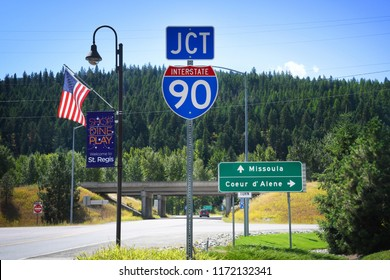 ST. REGIS, MONTANA, USA: September 1, 2018: An American flag and road and welcome signs at the juntion of Interstate 90 and Montana Highway 135