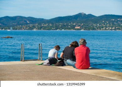ST TROPEZ, FRANCE - OCTOBER 24, 2017: Unknown family relaxing on pier in the St. Tropez bay