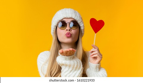 St. Valentine concept. Pretty girl in winter white hat and sunglasses holding red heart card and sending flying kiss, yellow background, panorama