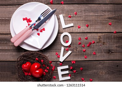 St. Valentine Day table setting. White plates in form of heart, cutlery, decorative hearts in nest and word love on  vintage textured  background. View from above. Selective focus.  Flat lay.