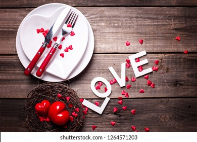 St. Valentine Day table setting. White plates in form of heart, cutlery, decorative hearts in nest and word love on  vintage  background. View from above. Selective focus. Place for text. Flat lay.