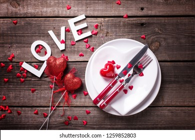 St. Valentine Day table setting.White plates in form of heart, cutlery, decorative hearts and word love on  vintage textured  background. View from above. Selective focus. Place for text. Flat lay.