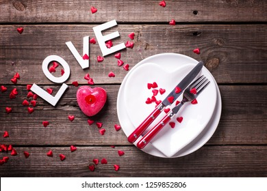 St. Valentine Day table setting.White plates in form of heart, cutlery, candle, word love on  vintage textured  background. View from above. Selective focus. Place for text. Flat lay.