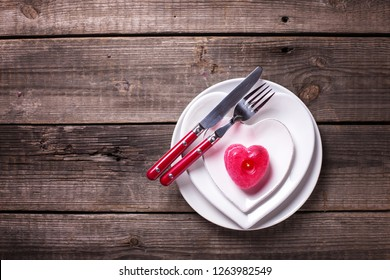 St. Valentine Day table setting.White plates in form of heart, cutlery, candle on  vintage textured  background. View from above. Selective focus. Place for text. Flat lay.