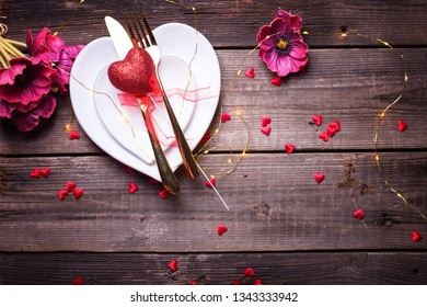 St. Valentine Day table setting.White plates in form of heart, cutlery, red  decorative heart, flowers,  fairy lights  on  vintage textured  background. View from above. Place for text. Flat lay.