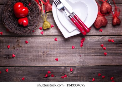 St. Valentine Day table setting.White plates in form of heart, cutlery, red and golden decorative hearts, hearts in nest on  vintage textured  background. View from above.  Place for text. Flat lay.