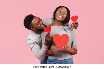 St. Valentines day concept. Black couple in love holding red valentines cards and embracing, pink studio background