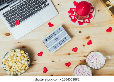 St. Valentine's day Movie night concept. Movie night message on board, laptop, popcorn, red candle, gift, hearts decor, two cups of cocoa with marshmallows for a couple. Cozy holiday plans for lovers