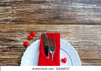 St Valentines Day place setting en white red tone. Plate, cutlery, line napkin, decorative heart on wooden background with copy space.  Love romantic dinner concept.