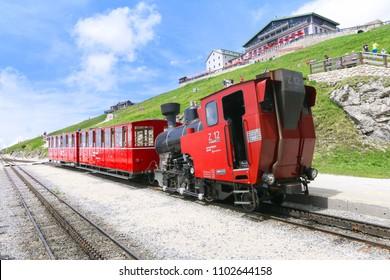ST WOLFGANG, AUSTRIA: MAY 27, 2018 - Schafberg railway train with Schafbergspitze Hotel in background. The SchafbergBahn is the steepest cogwheel railway in Austria.