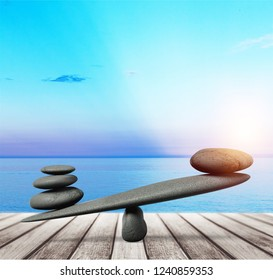 Stability scales with zen stones on light blue background