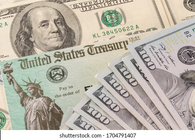 Stack of 100 dollar bills with illustrative coronavirus stimulus payment check to show the virus stimulus payment to Americans