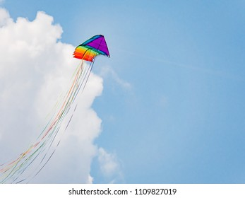 Stack of 16 2-line delta stunt kites with long tails in the colours of the rainbow flying.