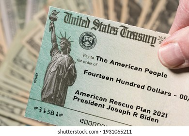 Stack of 20 dollar bills with US Treasury illustrative check to illustrate American Rescue Plan Act of 2021 payment on cash background - Shutterstock ID 1931065211