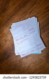Stack of 2018 W-2 IRS tax forms lying on a desk or table, waiting to be filled out. Lots of copy space