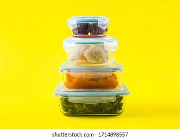 Pile de récipients de nourriture en verre hermétique avec des légumes cuits colorés sur fond jaune clair. Concept de préparation de repas