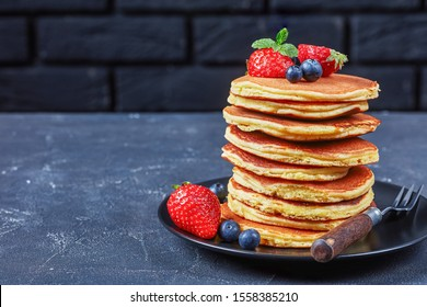 stack of almond flour pancakes on a black plate with strawberries, blueberries and mint on a concrete table with a black brick wall at the background, horizontal view from above. close-up, free space