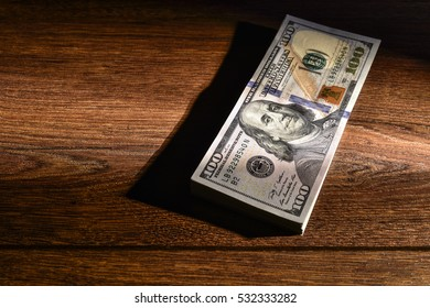 A stack of American dollars lie on wooden boards