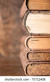 stack of antique  aged books on wooden table and background with interesting texture on butts