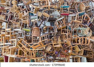 Stack of assorted metal and wooden chairs in random disarray, full frame furniture background image