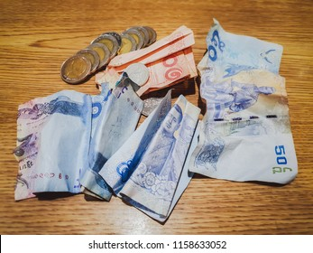 Stack of Baht banknotes and coins isolated. 10 Baht, 50 Baht, 100 Baht banknotes. Thai currency money banknotes on the table. Top view closeup. Salary, savings, Thailand union economic crisis concept.
