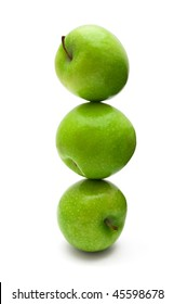 Stack of balancing green apples isolated on white