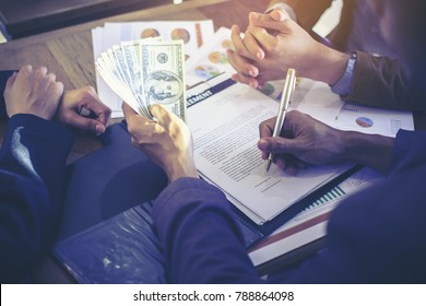 Stack of banknotes US dollars in the hands of young men. In his right hand holding a pen and signing documents on business deals by having a third party become a witness.