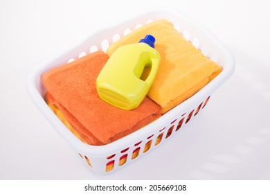 Stack of bath towels in basket, isolated on white background.