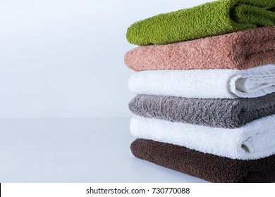 stack bath towels colorful textile background closeup on white