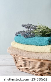 Stack of bath towels with lavender flowers in a wicker basket on light wooden background
