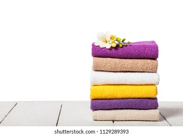Stack of bath towels on light wooden table and white background closeup